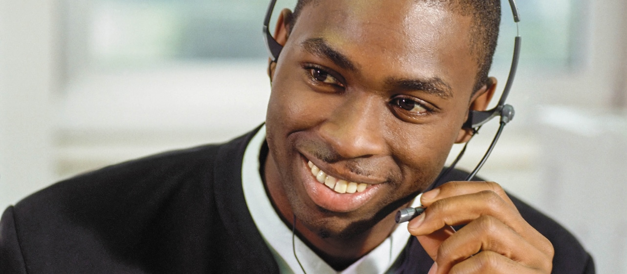 A Message Center man smiling and on the phone with a client