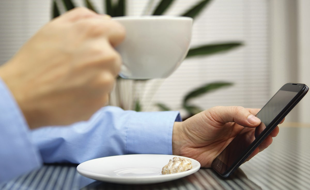 Close up of a man drinking his coffee and browsing his voicemails from A Message Center